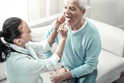 woman checking the senior man's mouth