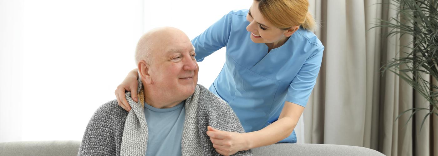 caregiver giving blanket to senior man